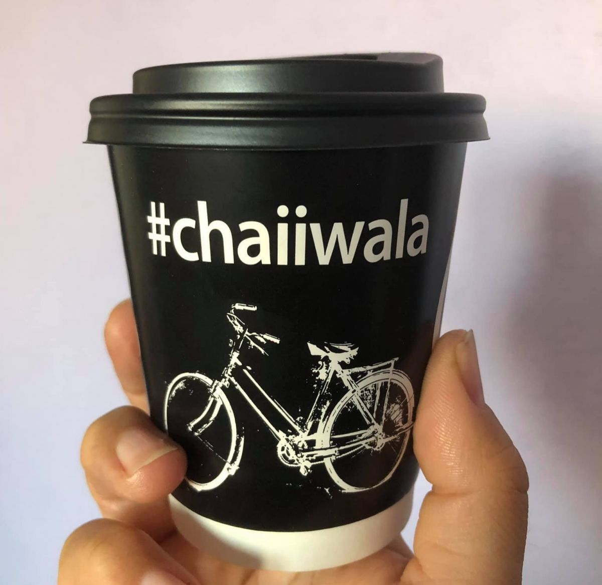 holding a cup of tea with chaiiwala logo