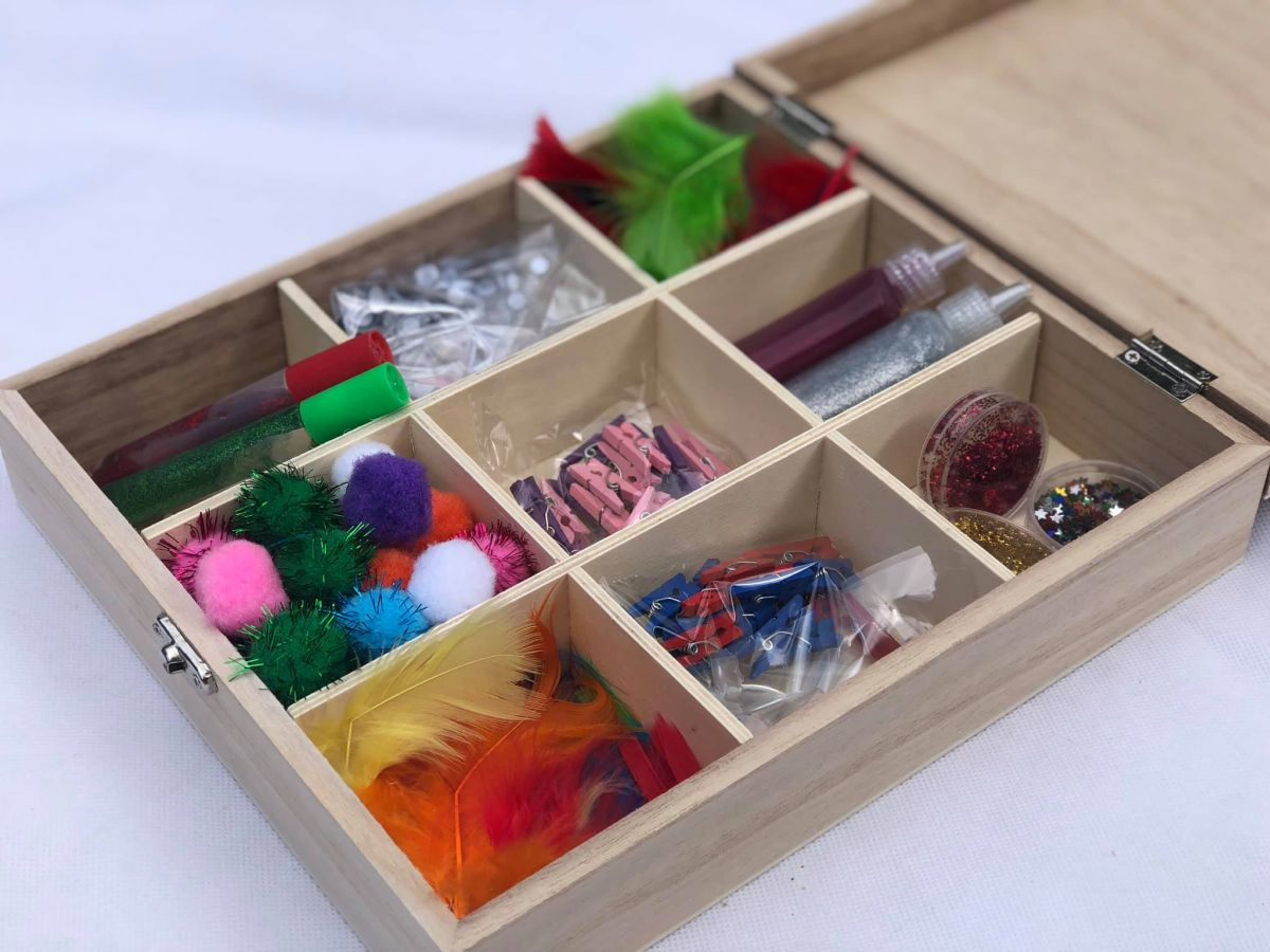 Personalised craft box open to show contents including feathers and googly eyes