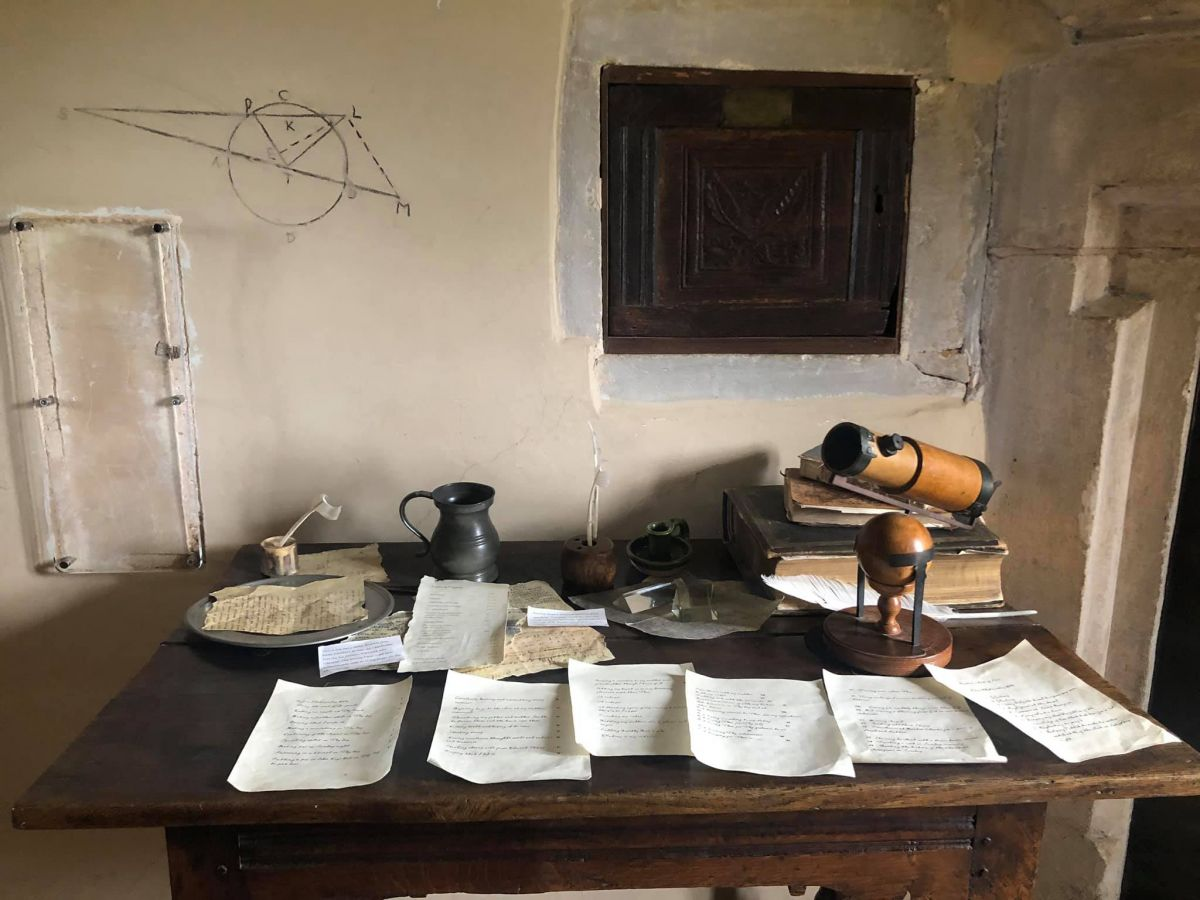 A desk where Isaac Newton did his work. Papers on the desk and writing on the wall